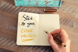 53239530 - retro effect and toned image of a woman hand writing a note with a fountain pen on a notebook. handwritten text stick to your core values as business concept image