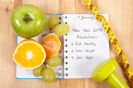 48840123 - new years resolutions eat healthy, lose weight and join gym written in notebook, fresh fruits, dumbbells for fitness and tape measure, healthy lifestyle