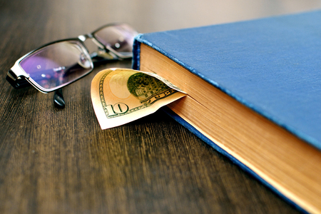 56352122 - old book with dollars bookmark and  glasses