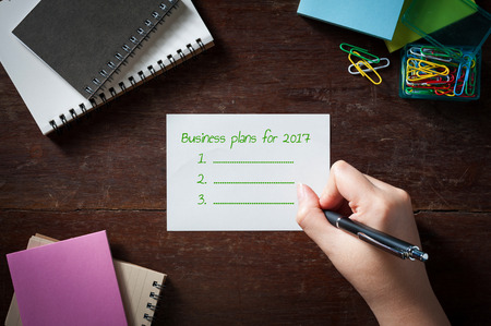 "63767321 - woman right hand writing ""business plan for 2017"" on notepad on wood table with low key scene"
