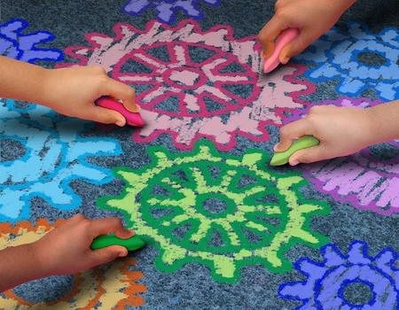 41506649 - education concept as a diverse community of children working together in friendship drawing connected gears and cog wheels with chalk as a symbol for the success of learning with a school program.