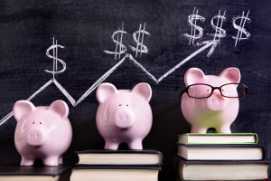 37342898 - three pink piggy banks standing on books next to a blackboard with simple savings progress chart. sharp focus on the piggy banks.